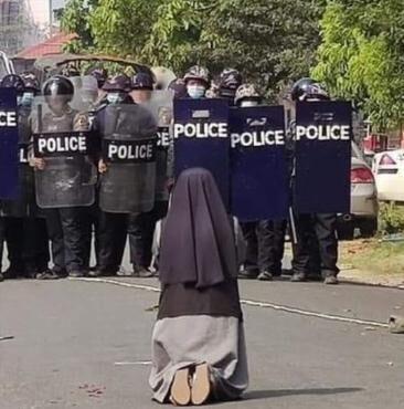 La polizia di Myammar viene trattenuta da una suora inginocchiata